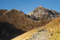 Mountain footpath. A footpath leads up past a grassy bank towards large mountainous cliffs with ridgelines and peaks Stock Photography