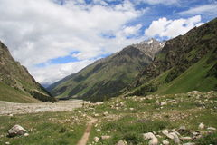 The mountain footpath leaving afar. The narrow mountain footpath passes between big majestic slopes of mountain tops of the Caucasus, about a track flowers grow Royalty Free Stock Images