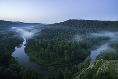Mountain forest landscape. Trees and the river in the fog in the early morning. Stock Image