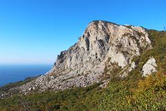 Mountain Foros on the Crimean coastline. View of Foros Mountain above the autumn forest on the Crimean Peninsula. It`s an unofficial name of the left part of stock photography