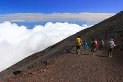 Mountain Fuji climbing and sea of clouds. Unidentified tourist at Mountain Fuji climbing and sea of clouds, Japan stock photos