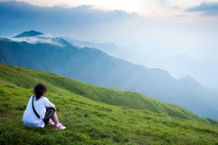 Mountain girl sitting in the lawn of view Royalty Free Stock Image
