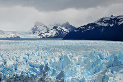 Mountain glacier. Perito Moreno Glacier, at the Patagonia, in Argentina, with mountains in the background Stock Photos