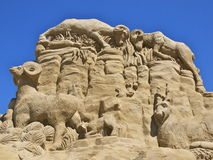 Mountain goats sand sculpture. Sand sculpture of fighting mountain goats, against a blue sky Royalty Free Stock Image