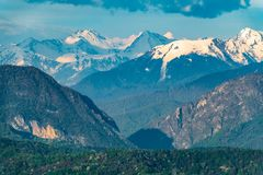 Mountain gorge with high mountains with snowy peaks. Dramatic cloudy sky over a mountain canyon royalty free stock image