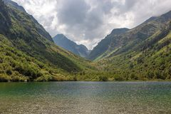 Mountain gorge in summer, green trees and a lake in the Caucasus, Dombay. With clouds in the sky Stock Images