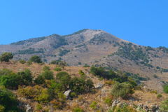Mountain in Greece. The mountain is covered lonely vegetation on the background of blue sky Royalty Free Stock Photos