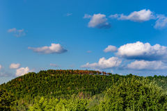 Mountain with green and red trees. Sky with clouds. stock photos