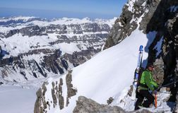 Mountain guide on a backcountry ski tour rappelling down into and through a narrow snow-filled couloir for an extreme ski descent. A mountain guide on a royalty free stock photography