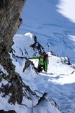Mountain guide on a backcountry ski tour rappelling down into and through a narrow snow-filled couloir for an extreme ski descent. A mountain guide on a Royalty Free Stock Image