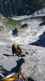 Mountain guide on a hard granite climb to a high alpine peak in the Swiss Alps. Male mountain climber and rock climber on the very hard and steep Via Cassin on Stock Image