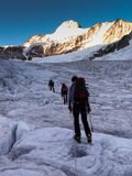 Mountain guide leads his clients over a glacier on their way to a high alpine summit after an early morning start. A mountain guide leads his clients over a Royalty Free Stock Photos