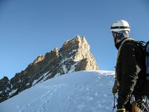 Mountain guide looks towards the summit and the ascent route of a high summit in the Swiss Alps near Zermatt Stock Photo
