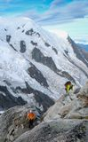 Mountain guide and a male client on a rocky ridge heading towards a high summit in the French Alps near Chamonix Stock Images