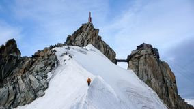 Mountain guide and a male client on a snow ridge heading down from a high summit in the French Alps near Chamonix Stock Photo