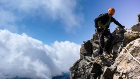 Mountain guide on a steep and exposed rocky ridge on his way to a high alpine summit with a client. A mountain guide on a steep and exposed rocky ridge on his Stock Image