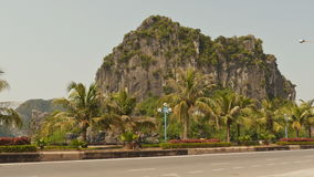 Mountain Ha Long Bay on the road against a passing car. North Vietnam. stock footage