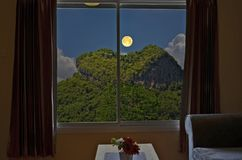 Mountain heath with full moon in window view. Of resort in the evening Stock Image