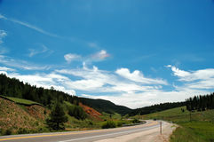 Mountain Highway and Rainbow Cloud. Rainbow cloud above mountain highway with deep blue sky Royalty Free Stock Photos