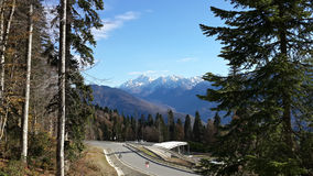 A mountain highway and snow-capped peaks. Autumn in the mountains of Krasnaya Polyana, a mountain highway, coniferous trees and snow-capped peaks of the Caucasus Stock Photo
