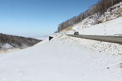 Mountain  highway among snow slope ,   Altai, Russia Stock Photography
