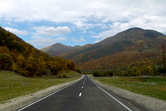 Mountain highway. Highway in the valley of the mountains covered by autumn forest royalty free stock photography