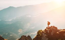 Mountain hiker with backpack tiny figurine stay on mountain peak with breathtaking hills panorama royalty free stock photos