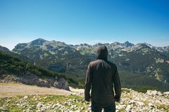 Mountain hiker at high viewpoint looking at the valley. Male tourist person in hooded jacket at mountain top enjoying the view royalty free stock image