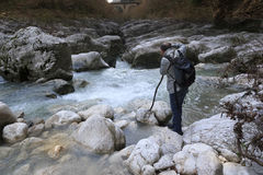 Mountain hiker river. Hiker in a canyon with bridge in the background Stock Image