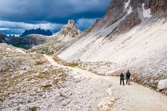 Mountain hikers with trekking poles walks on the rocky path in the mountains. Nordic walking theme.  royalty free stock images