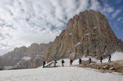 Mountain hikers walking at peak base. Distant hikers walking beside a rocky mountain peak Stock Photos
