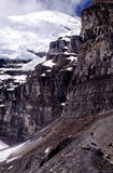 Mountain hiking. A view of a distant hiker, walking along steep cliffs and a boulder-strewn trail on the Plain of Six Glaciers in Banff National Park, Alberta Royalty Free Stock Images