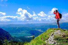 Mountain Hiking. Hiking on top of the mountain contemplating nature / Woman on the mountain top with blue sky and green grass