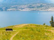 Mountain hiking trail  with bench overlooking the lake Stock Image