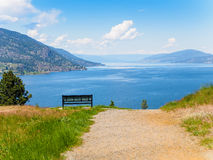 Mountain hiking trail  with bench overlooking the lake Stock Photo