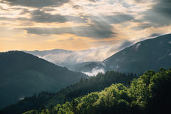 Mountain hill with fog and sunbeam at sunrise Royalty Free Stock Photos