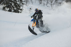 Mountain horse husaberg  on a motorcycle in winter forest in the mountains. SAKHALIN RUSSIAN - JANUARY 23 :Kosty Glushko moving mountain horse husaberg  on a Stock Photos