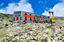 Mountain Hostel under Rysy and tourists in Slovak Tatra Mountains. Stock Photo