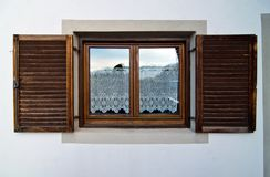 Mountain house window with wooden shutters and glass lace. Mountain home window with traditional wooden shutters and curtains with handmade lace to the glass Stock Photography