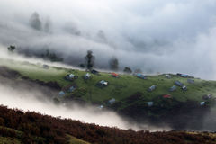 Mountain houses in foggy weather Stock Photo
