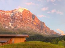 Mountain hut with alpenglow, Switzerland. Alpenglow over mountain hut near Grindelwald in valley at sunset in front on mountain Eiger north face, Switzerland Royalty Free Stock Images