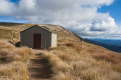 Mountain hut on grassy hill Royalty Free Stock Image