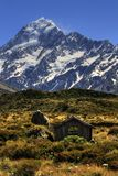 Mountain hut Mt Cook. Mount Cook towering in the background of an old mountain hut royalty free stock photos