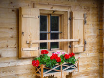 Mountain-hut window. Rustic wooden mountain hut window with red flower box and shutter Stock Photography