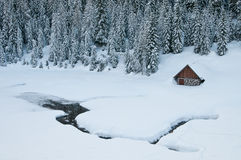 Mountain hut in winter. With forest in the background Stock Images