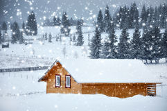 Mountain hut in winter with snowflakes. Christmas concept Royalty Free Stock Image