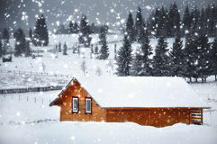 Mountain hut in winter with snowflakes. Christmas concept Stock Photos