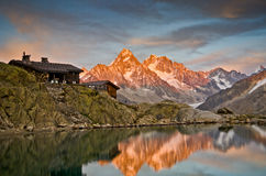 Mountain huts with lake reflection Stock Images