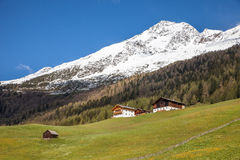 Mountain huts and snow-capped mountains Stock Image