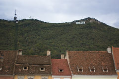 The mountain with inscription sign Brasov and the old city red roofs. Romania Stock Image